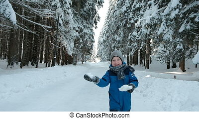 Boy in blue overalls running on road winter forest with snowballs.