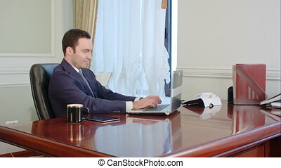 Young businessman looking at computer monitor during working...