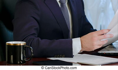 Businessman signing documents with a cup of coffee on the table