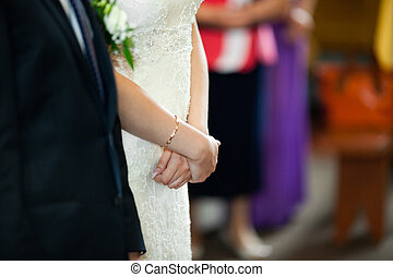 Bride holds her hands closed during the ceremony in church