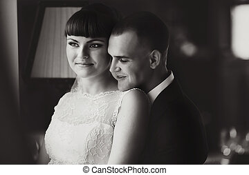 Smiling groom leans on bride's shoulder hugging her from behind