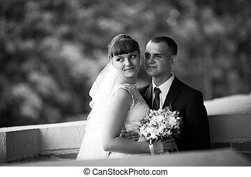 Bride looks far away standing in groom's hugs on the brick...