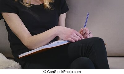 Smart young woman making notes with joy.