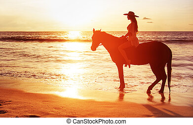 Beautiful brunette lady riding a horse and watching a sunset