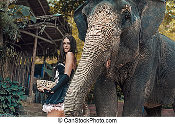 Brunette elephant trainer feeding her pet - Brunette...