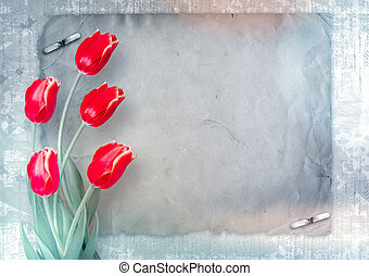 Bouquet of red tulips with green leaves on abstract paper...