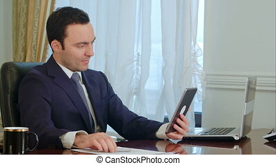 Handsome businessman has meeting on tablet with documents on...