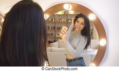 Young pretty girl takes a photo of herself before the mirror. she in the beauty salon with fantastic reflection in her eyes