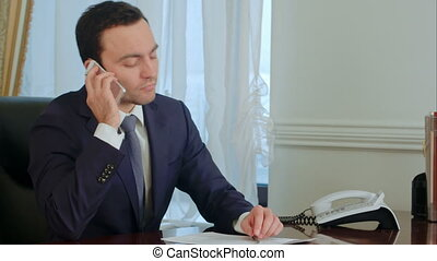 Young serious businessman take a phone call, having a conversation and getting pensive