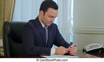 Businessman working with smartphone by desk in the office....