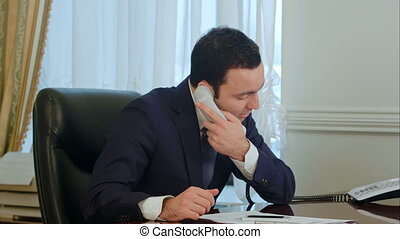 Businessman finish calling and start working with documents...