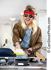 Rockstar selling tickets - Rockstar with a guitar holding...