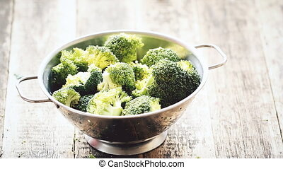 Fresh broccoli in stainless steel colander on old wooden...