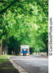Blurred image of truck driving on asphalt road, vertical...