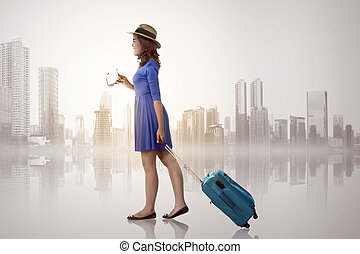 Young asian woman with hat holding suitcase over cityscape...