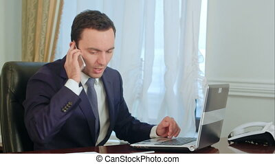 A young attractive businessman working at his desk, takes a phone call, makes notations, drinking coffee