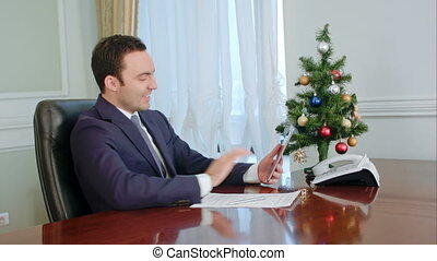 Young businessman makes call by tablet, smiling,...