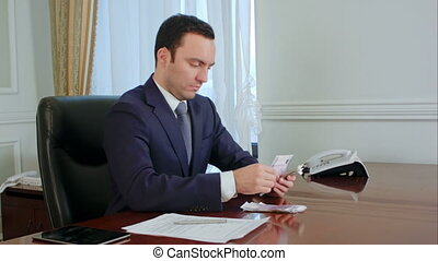 Confident young businessman counting money and planing the...