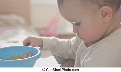 Child plays with food - Close up of small child eat...