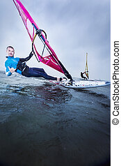 windsurfer greeting with shaka - windsurfer at speed with a...