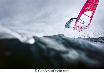 freestyle windsurfer in a huge splash - professional surfer...
