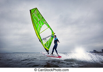 Freestyle windsurfer does a trick on the lagoon -...