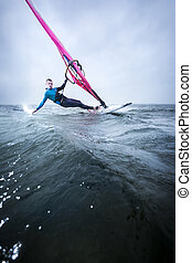 hanging in the storm, touching the water - windsurfer...