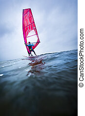 surfer on a lake catching the wind - windsurfer at the open...