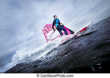 windsurfer carves and tilts the rig - A windsurfer tilts the...