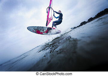 Windsurfer stunting on waves - Windsurfer making a jump