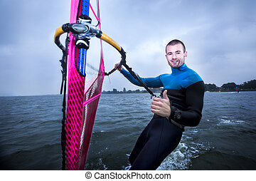 happy windsurfer gives a thumbs up - windsurfer enjoying the...