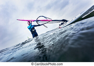 windsurfer waiting for the wind - surfer standing in the...