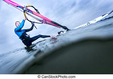 overunder of a windsurfer ready to go - surfer standing in...