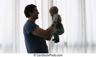 Father kisses baby, silhouette