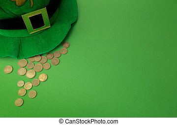 Happy St Patricks Day leprechaun hat with gold coins on green background. Top view