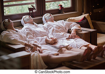 women is getting facial clay mask at spa