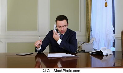 Businessman having trouble while phoning and puts the phone...