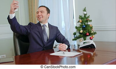 Boss taking funny selfies with New Year Tree, smiling