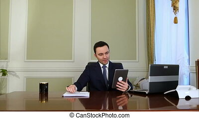 Businessman chatting on tablet computer and doing paperwork...