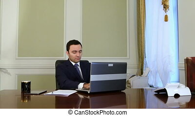 Someone disturbs businessman work, but he continues work with laptop