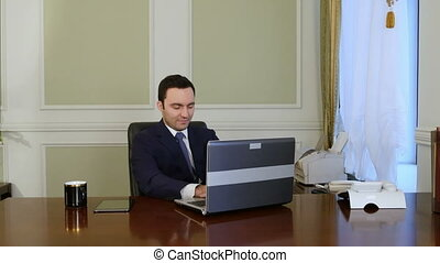 European worker typing on keyboard and looking at monitor of...