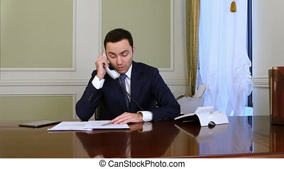 Serious businessman discuss problem by landline phone and becomes disappointed