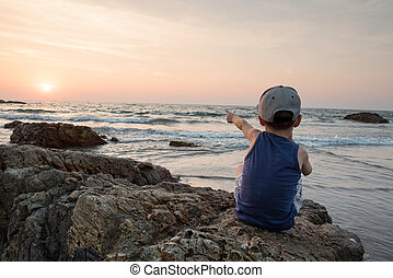 young boy standing pointing into the sky in front of sea