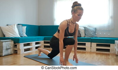 In the home environment a woman sit on a mat and puts his leg back.