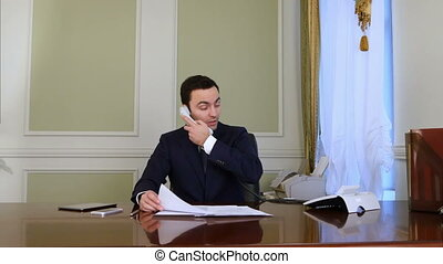 Overworked businessman attending phone calls and doing...