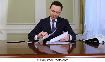 Pensive businessman sign documents turning over the sheets....