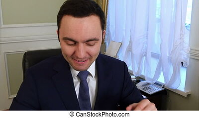Portrait of happy young businessman reading paperwork at desk in office and smiling
