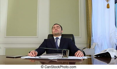 Overworked businessman falling asleep in office....