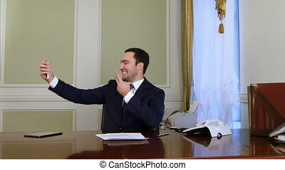 Happy businessman taking selfie photo with cellphone in...