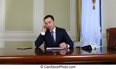 Businessman looking tired and talking on cellphone while...